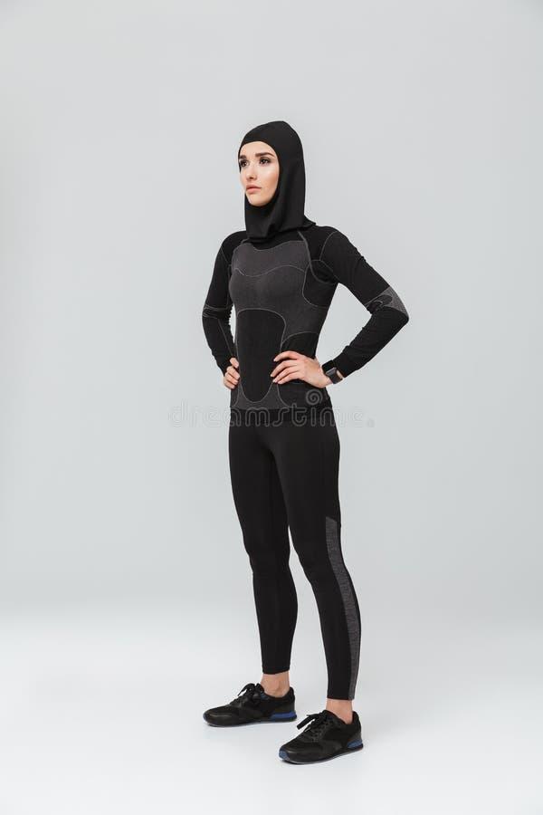 Musulmani di forma fisica della giovane donna che posano sopra il fondo bianco della parete immagini stock