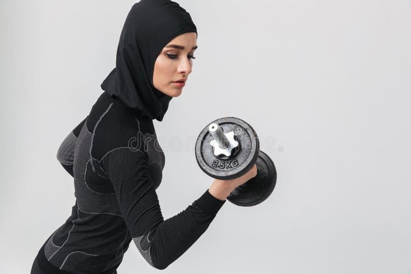 Musulmans de forme physique de femme posant au-dessus du fond blanc de mur pour faire des exercices avec l'haltère photographie stock