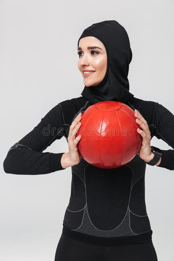 Musulmans de forme physique de femme posant au-dessus du fond blanc de mur pour faire des exercices avec la boule photographie stock libre de droits