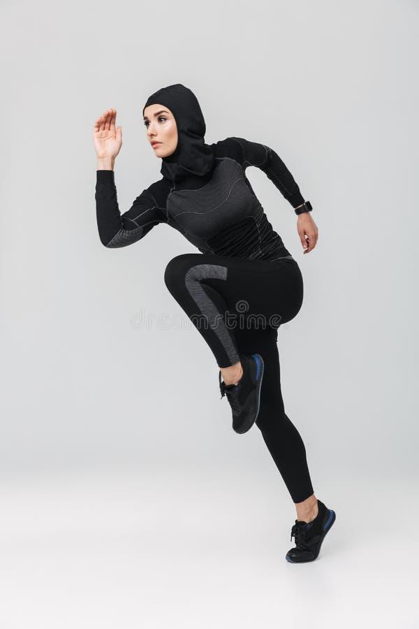 Musulmans de forme physique de femme posant sauter de fonctionnement d'isolement au-dessus du fond blanc de mur photos stock