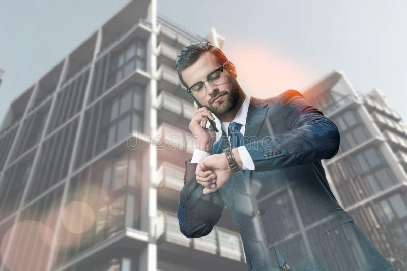 Muszę być tam w czasie Ruchliwie przystojny biznesmen chodzący opowiada telefonem i patrzeje jego zegarek podczas gdy zdjęcie royalty free