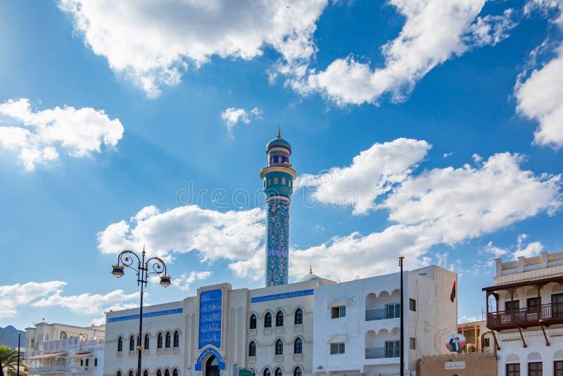Muszkat Oman, Grudzień, - 17, 2018: minaret nad domami na miasto ulicie obrazy royalty free