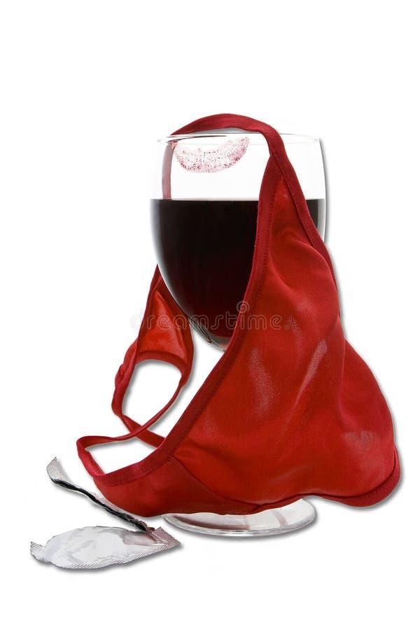 Mutandine, vetro di vino ed involucro del preservativo fotografia stock