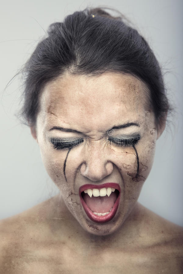 Mutation of vampire. Female vampire with burnt skin on a gray background. Artistic colors added stock photography