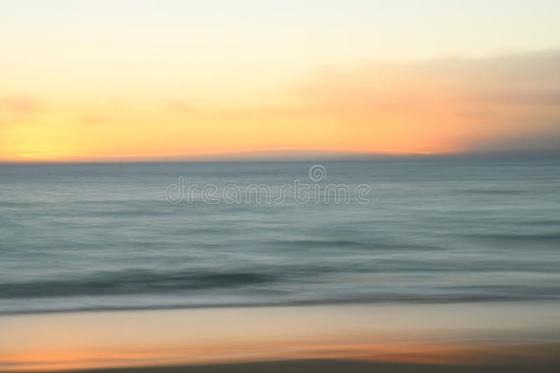 Muted Motion Blur Background of Sunset Over Ocean and Beach. Motion blur sunset over ocean with orange glow reflecting in sand on beach in foreground stock images