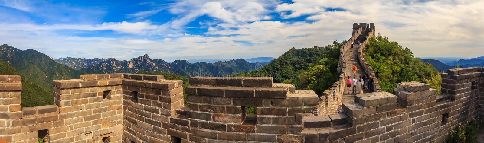 MutianyuPanoramic view of the Great Wall of China and tourists walking on the wall in the Mutianyu royalty free stock photography
