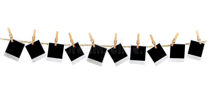 Mutiple unbelegte polaroidfelder, die durch Clothesp hängen lizenzfreie stockfotos