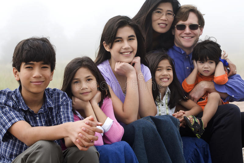 Mutiracial Familie, die auf Strand sitzt lizenzfreie stockbilder