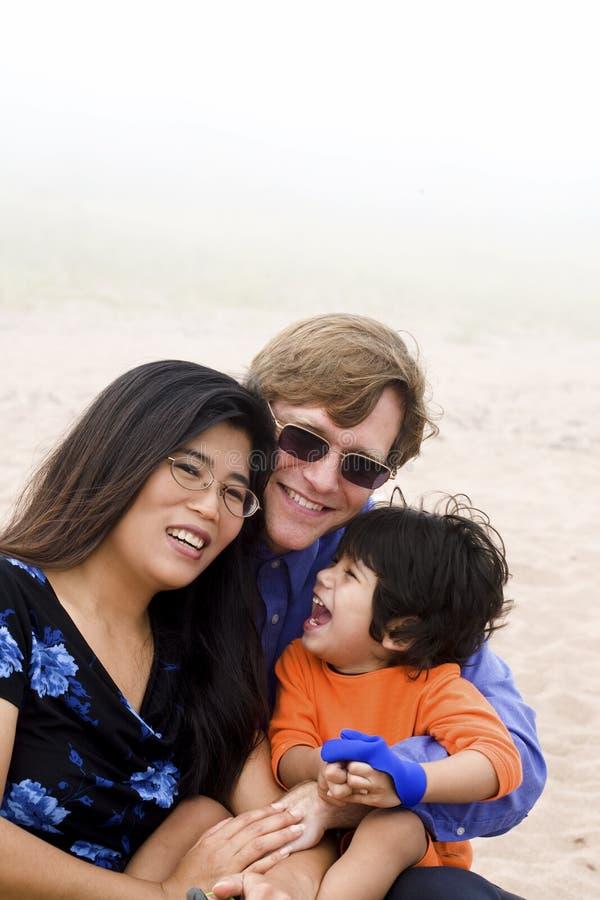 Mutiracial Familie, die auf Strand sitzt stockfotos