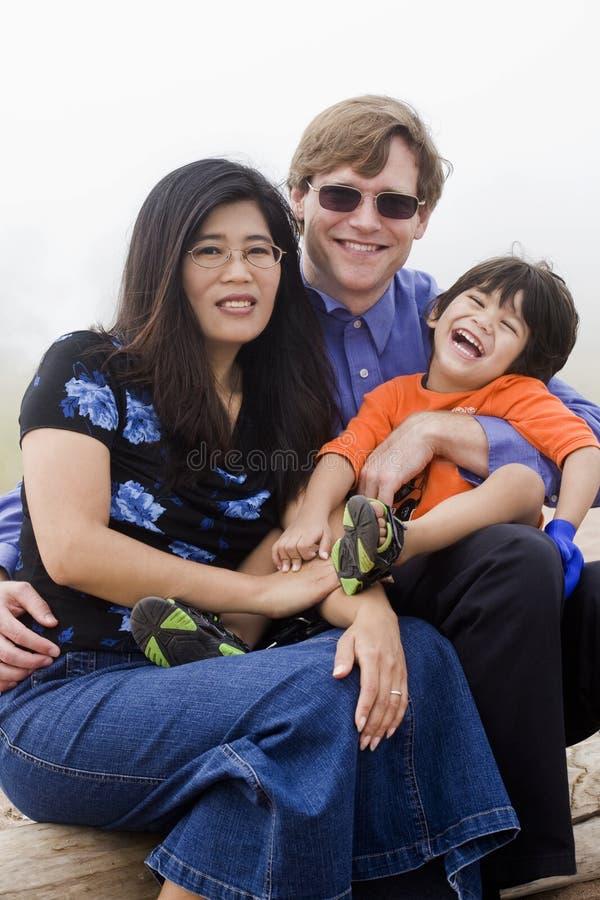 Mutiracial Familie, die auf Strand sitzt lizenzfreies stockbild