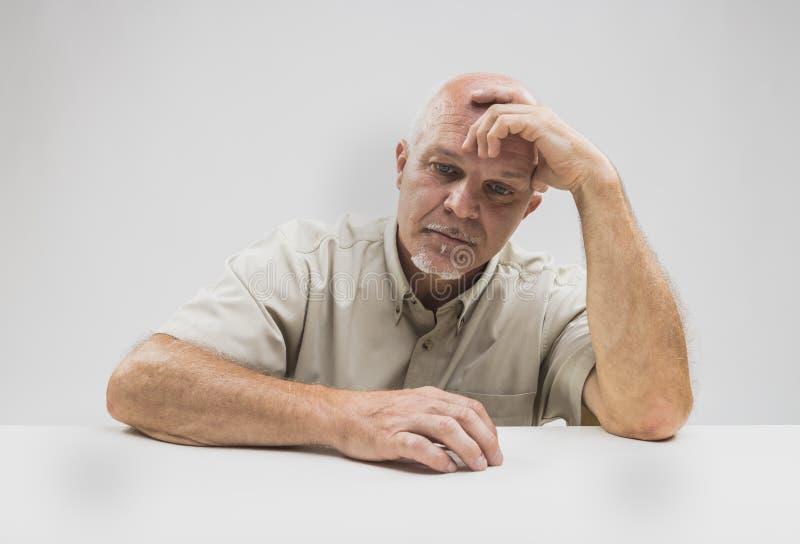 Mutloses sitzendes Denken des älteren Mannes stockfotografie