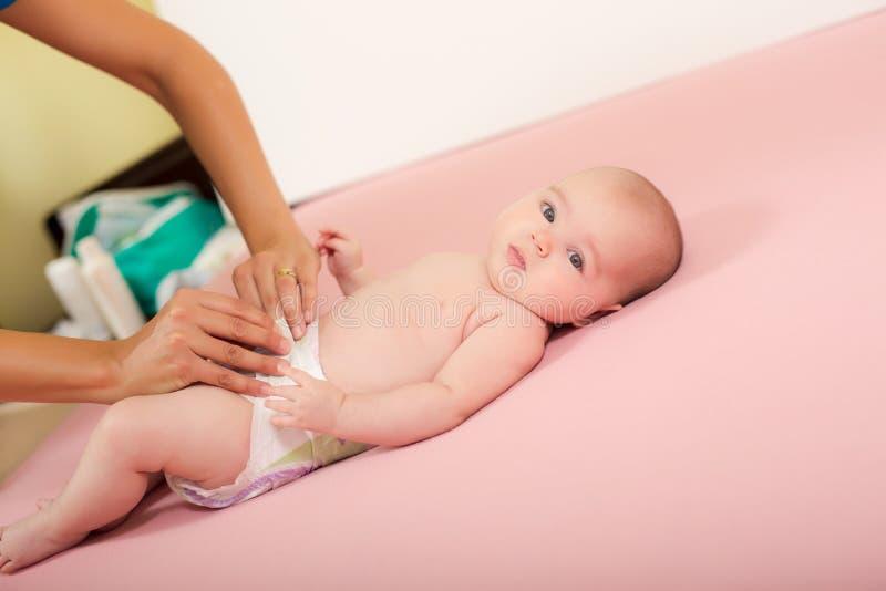 Mutter ändert die Windel ihres Babys lizenzfreie stockfotos