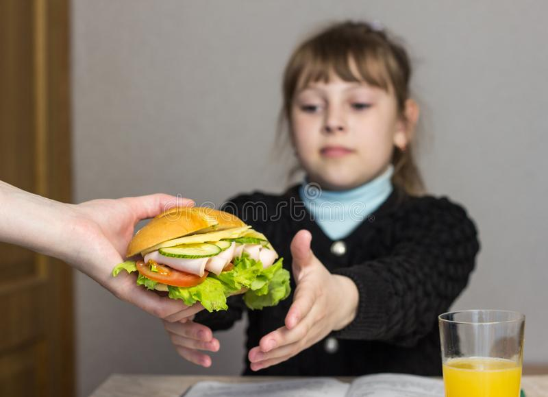 Mutter bereitet ein Sandwich für ein Kind in der Schule, Schulmädchen zu, lizenzfreies stockfoto