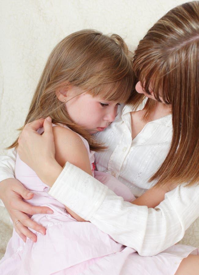 Mutter beruhigt die schreiende Tochter stockfotografie