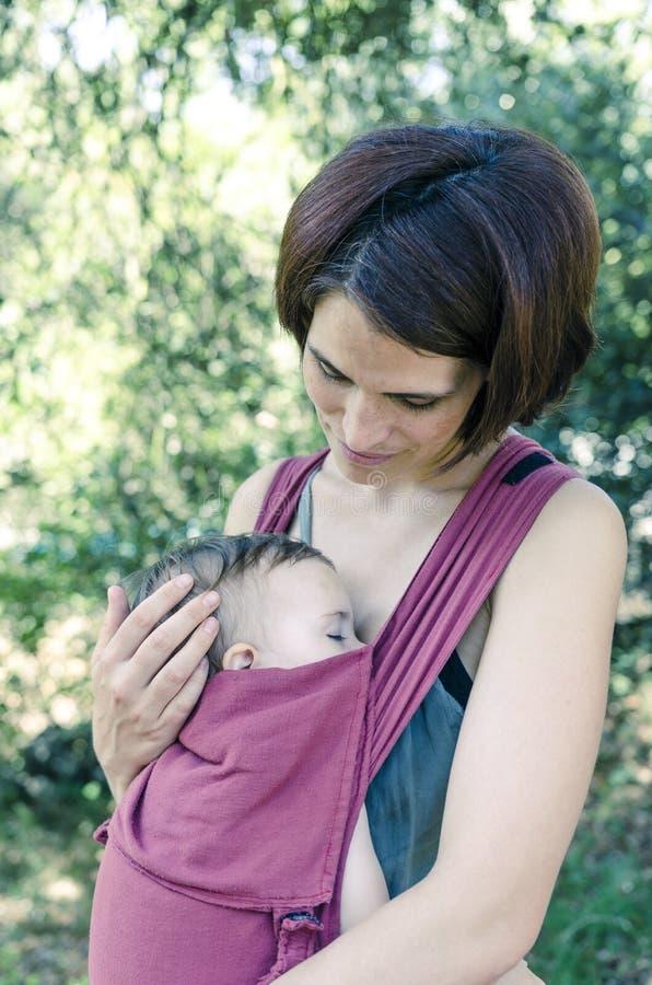Mutter betrachtet ihr Baby, das auf einer Babytrage schläft stockfotografie