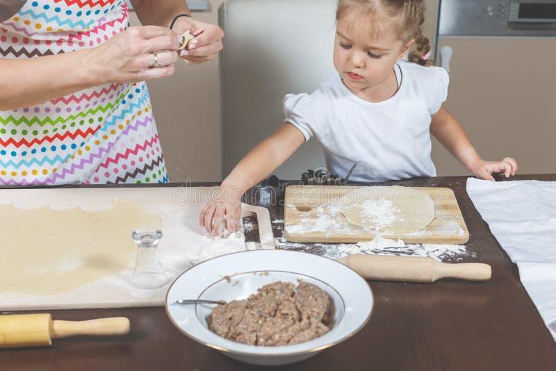 Mutter des kleinen Mädchens Hilfsmachen Mehlklöße stockbilder