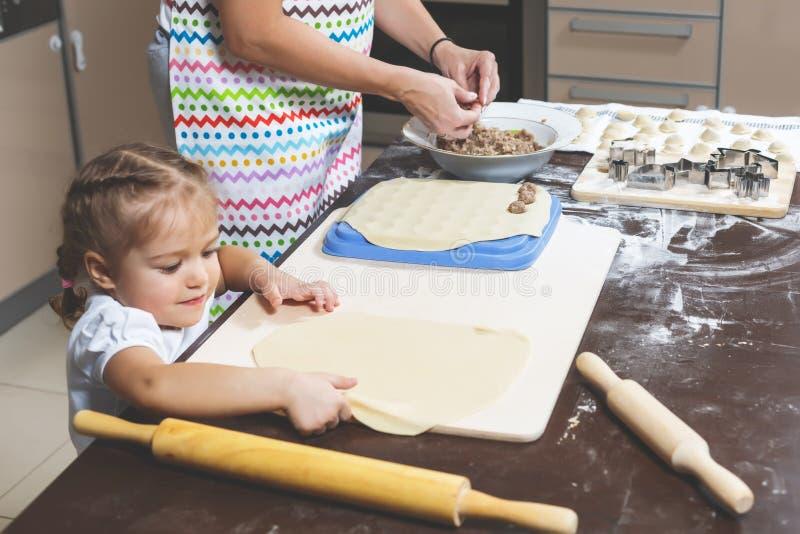 Mutter des kleinen Mädchens Hilfsmachen Mehlklöße zu Hause lizenzfreie stockfotografie