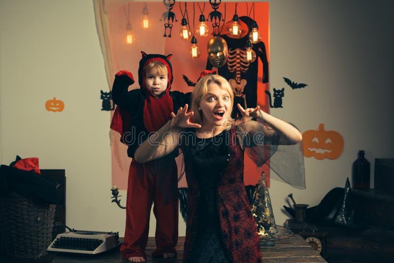 Mutter, die als Hexe, Sohn trägt als Teufel trägt Junge im Teufelkostüm Schöne junge Frau mit einem Kind mit Kürbisen stockfotos
