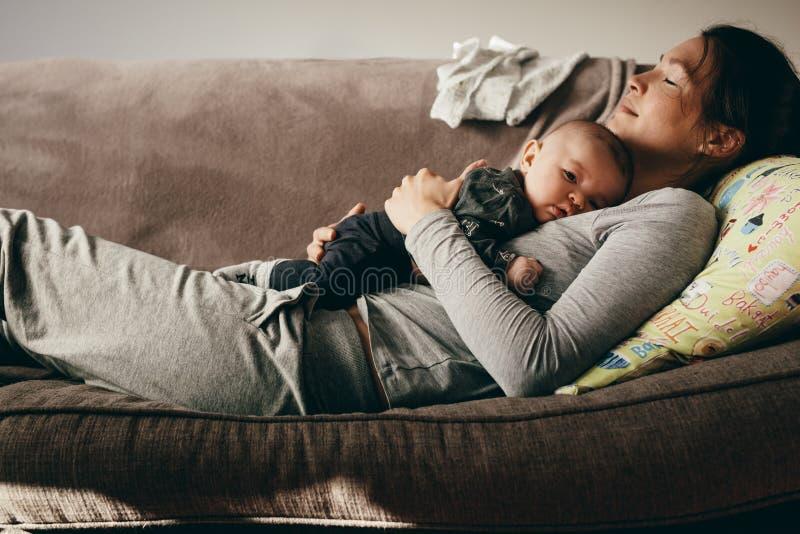 Mutter, die auf einer Couch mit ihrem Baby auf ihr schläft lizenzfreie stockfotografie