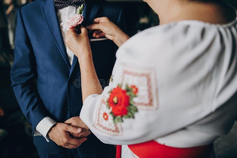 Mutter, die auf stilvollen Bräutigam in blauen Klage Boutonniere mit rosa Rosen in Hotelzimmer sich setzt Morgenvorbereitung vor  lizenzfreie stockbilder