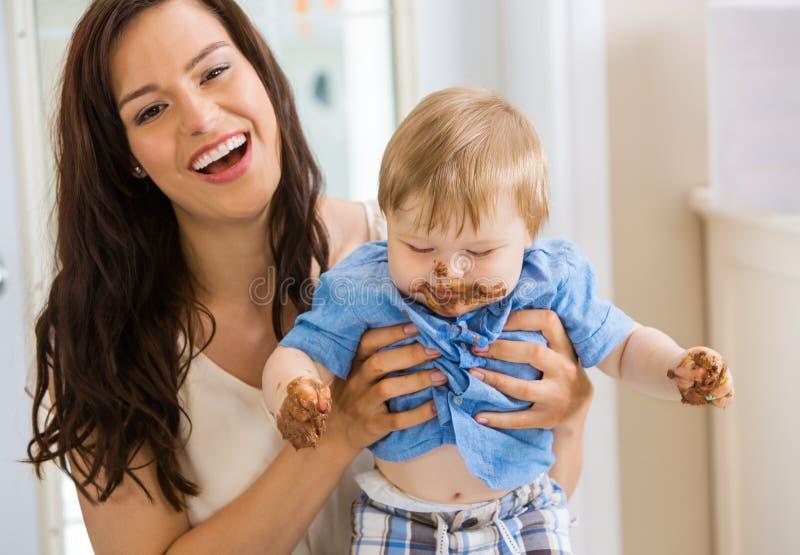 Mutter, die Baby mit Kuchen-Zuckerglasur auf Gesicht hält stockfotos