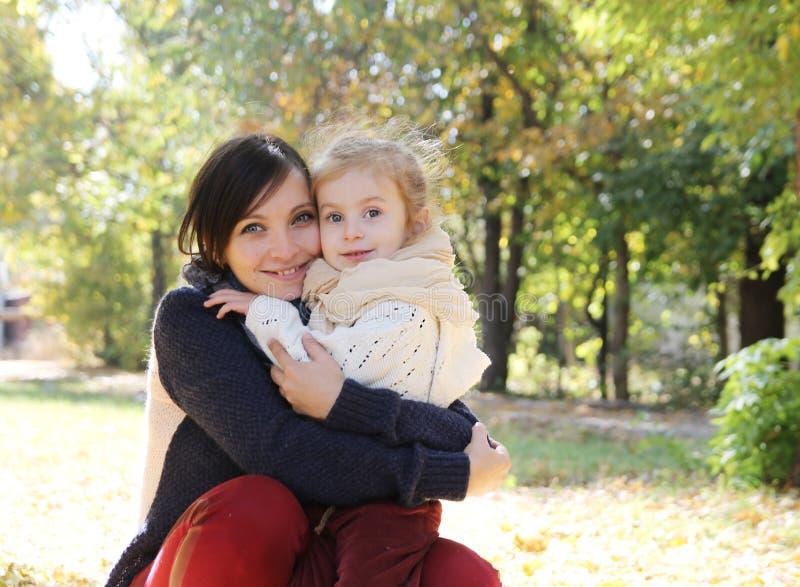 Mutter, die Babytochter im Herbstpark umarmt stockfoto
