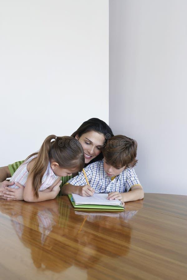 Mutter, die bei Tisch Kinder in der Hausarbeit unterstützt stockbild