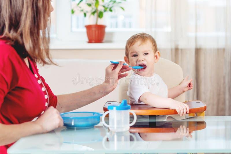 Mutter, die das Baby heraus hält ihre Hand mit einem Löffel der Nahrung in der Küche einzieht Gesunde Säuglingsnahrung lizenzfreie stockfotografie
