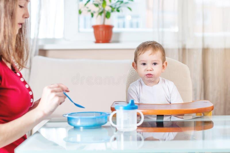 Mutter, die das Baby heraus hält ihre Hand mit einem Löffel des Breis in der Küche einzieht Gefühle eines Kindes beim Essen lizenzfreies stockfoto