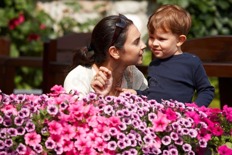 Mutter, die dem Kind im Freien erklärt stockbilder