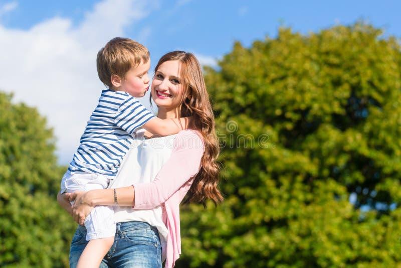 Mutter, die den Sohn in den Armen ihn küssend hält lizenzfreie stockfotografie