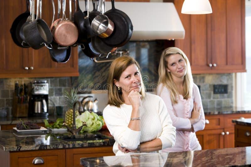 Mutter, die in der Küche mit jugendlicher Tochter steht lizenzfreie stockbilder