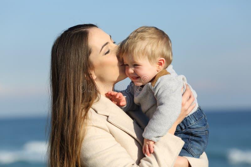 Mutter, die draußen ihren Kindersohn küsst stockfoto