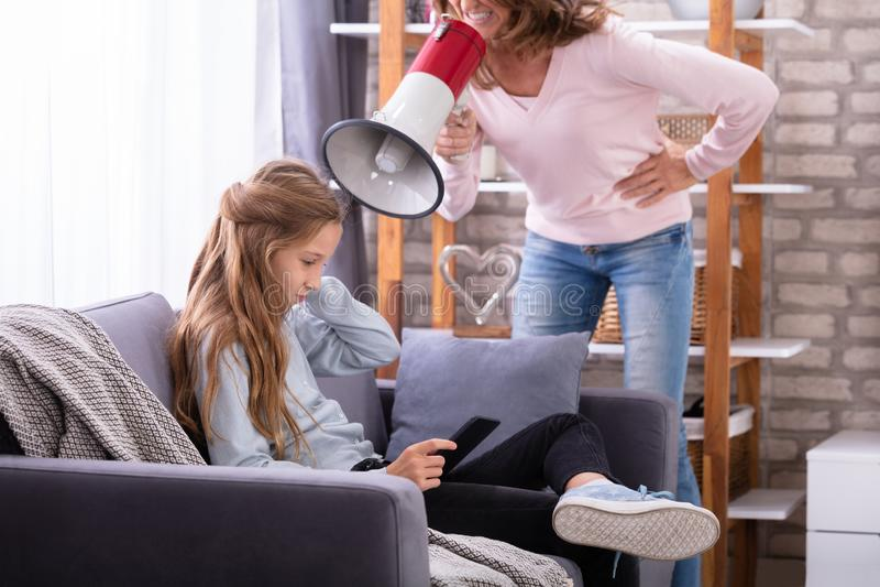 Mutter, die durch Megaphon am M?dchen unter Verwendung Digital-Tablets schreit stockfotografie