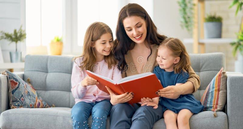 Mutter, die ein Buch zu ihren T?chtern liest lizenzfreie stockfotos
