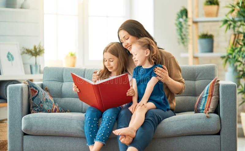 Mutter, die ein Buch zu ihren T?chtern liest stockfoto
