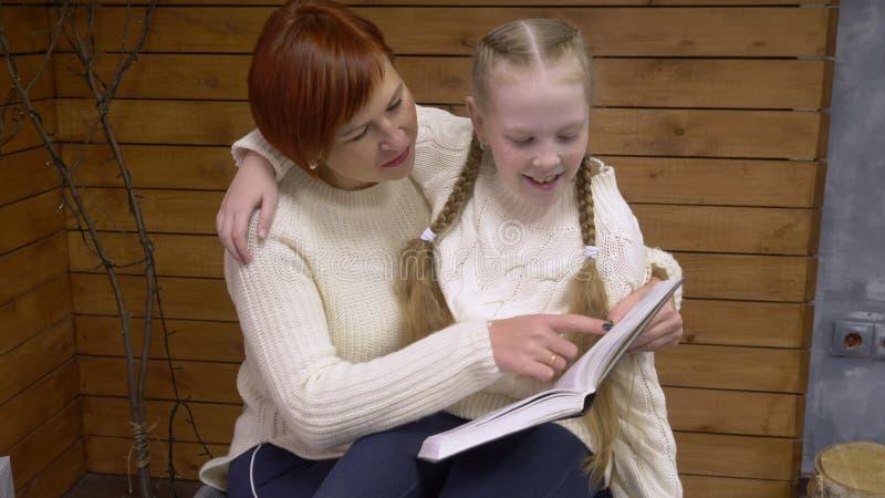 Mutter, die ein Buch zu ihrer Tochter liest lizenzfreies stockfoto