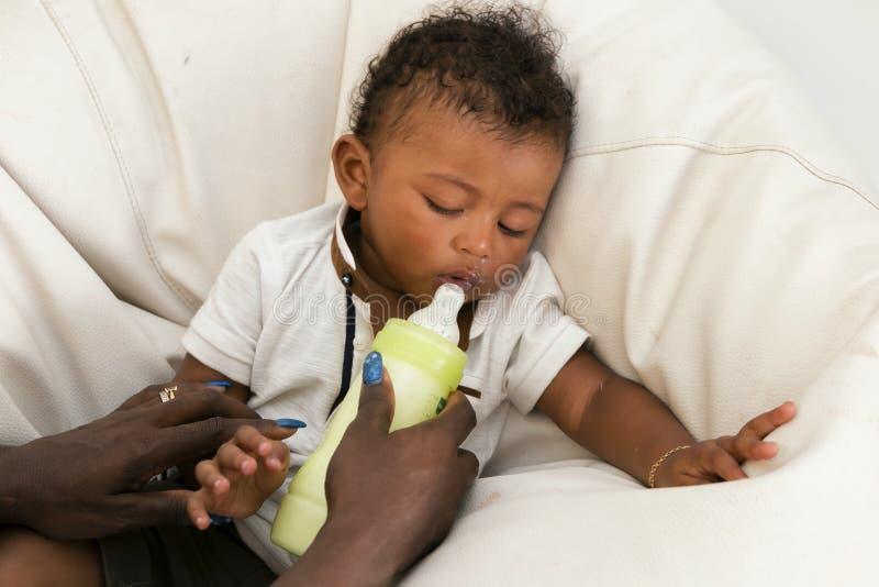 Mutter, die ein Säuglingskind mit Milch einzieht stockfotografie