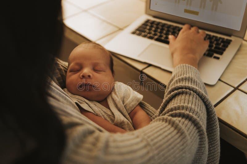 Mutter, die einen Computer verwendet und ihr Baby hält stockbilder