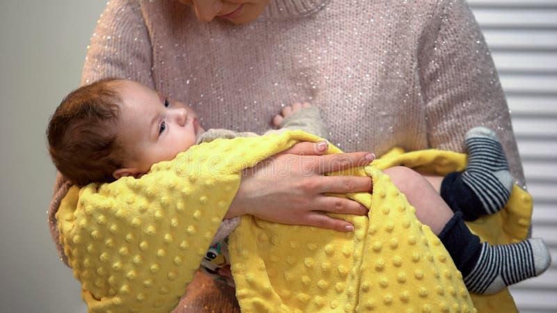 Mutter, die entzückendes neugeborenes, Gesangwiegenlied hält, um Baby, glückliche Mutterschaft zu beruhigen lizenzfreies stockfoto