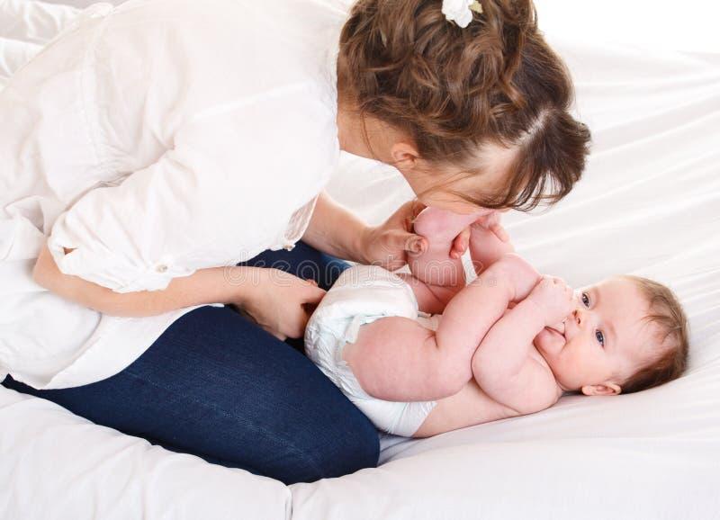 Mutter, die Fuß des Schätzchens küßt lizenzfreies stockbild