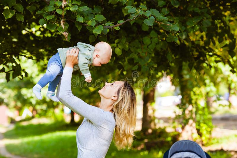 Mutter, die ihr Baby über ihrem Kopf hält stockbild