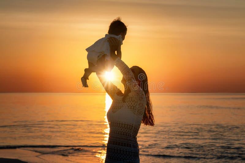 Mutter, die ihr Baby in der Luft auf einem Strand hält lizenzfreie stockbilder