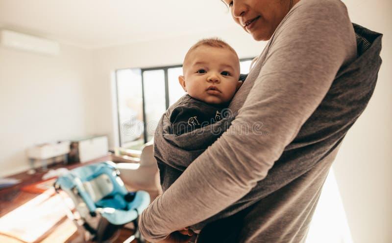 Mutter, die ihr Baby in einer Babyverpackungsfördermaschine trägt lizenzfreies stockbild