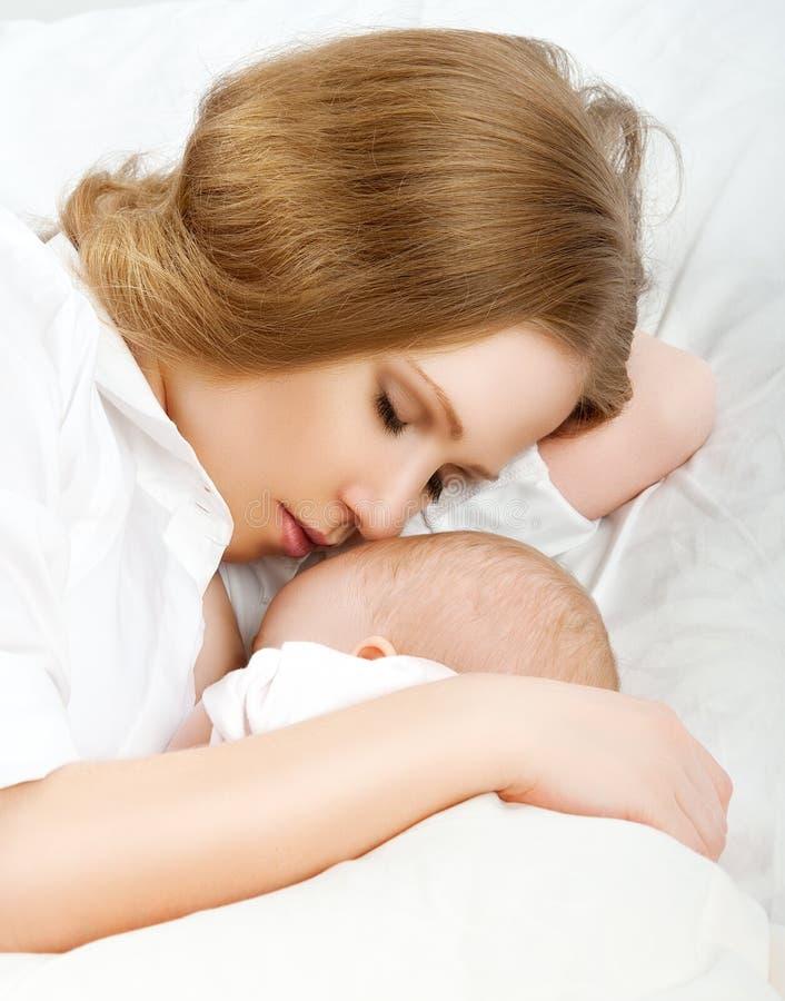Mutter, die ihr Baby im Bett einzieht. zusammen schlafen lizenzfreie stockfotografie