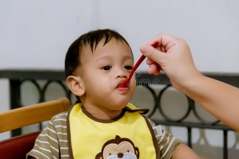 Mutter, die ihr Baby mit L?ffel einzieht Bemuttern Sie gesundes Lebensmittel zu Hause geben ihrem entz?ckenden Kind lizenzfreie stockfotos
