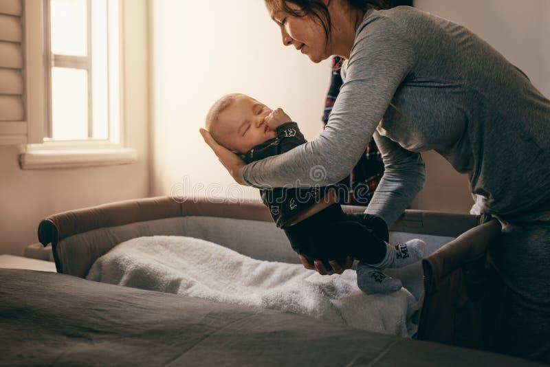 Mutter, die ihr Baby setzt, um auf einer Kopfendebabykrippe zu schlafen lizenzfreies stockbild