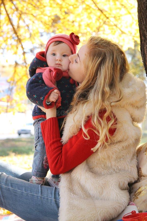 Mutter, die ihr Baby unter Herbstbaum küsst stockfotografie