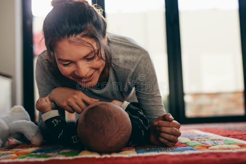 Mutter, die ihr Baby verwöhnt lizenzfreies stockfoto