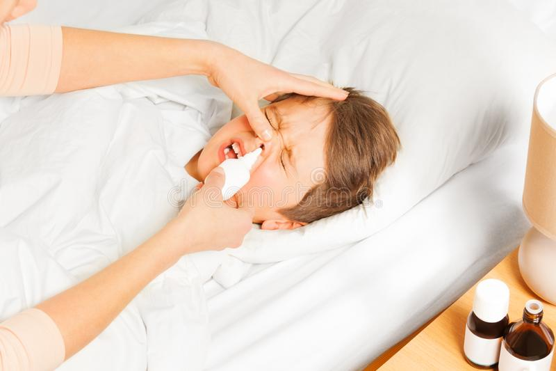 Mutter, die ihr Kinderjungennasenspray in der Nase spr?ht stockbild
